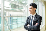 Asain businessman looking out of window