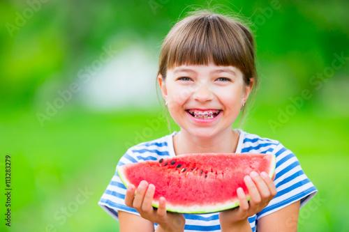 Leinwandbild Motiv Child eating watermelon. Kids eat fruits in the garden. Pre teen girl in the garden holding a slice of water melon. happy girl kid eating watermelon. Girl kid with gasses and teeth braces.