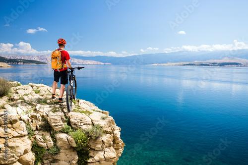 Mountain biking rider looking at inspiring sea and mountains