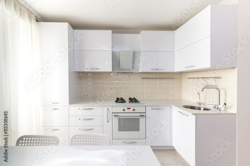 White glossy modern kitchen with stone countertop and built in household appliances in light colors interior