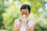 Girl blowing her nose with handkerchief while sneezing