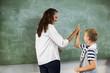 Happy teacher and school boy giving high five in classroom