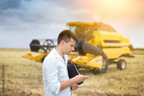 Businessman with laptop and cell phone in front of combine harve © Budimir Jevtic