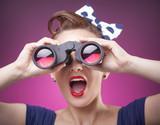 Fototapety Pin Up girl loking through binoculars on pink background