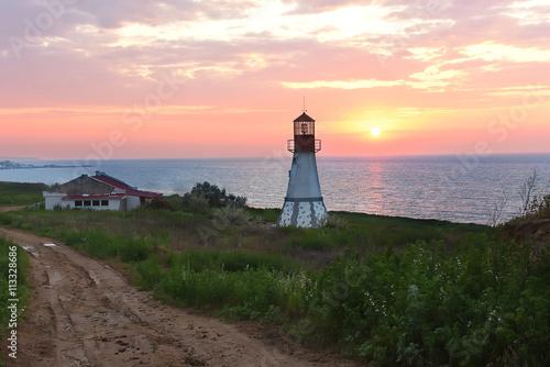 Fototapeta Lighthouse on the coast. beautiful sunrise, the sun is above the horizon, green vegetation around the lighthouse. Dark