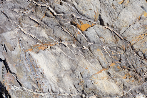 Uneven stone texture background with yellow lichen