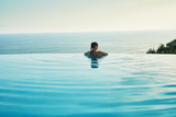 Fototapety Luxury Resort. Woman Relaxing In Infinity Swimming Pool Water. Beautiful Happy Healthy Female Model Enjoying Summer Travel Vacation, Looking At Sea View. Summertime Recreation, Relax And Spa Concept.