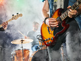 Rock band performs on stage. Guitarist, bass guitar and drums. Guitarist in the foreground. Close-up.