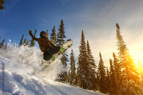 Jumping snowboarder on snowboard in mountains in ski resort Poster