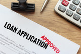 Approved loan application with rubber stamp and calculator