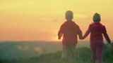 Boy with girl are holding hands on a background of a sunset on the green summer lawn. Slow motion.