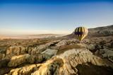 Hot air balloon flying over volcanic rock landscape, Cappadocia, Turkey