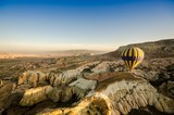 Hot air balloon flying over volcanic rock landscape, Cappadocia, Turkey