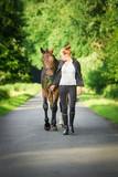 Junge, hübsche Reiterin führt Pferd am Halfter einen Weg entlang - 113374837
