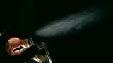 Spraying perfume against black background super slow motion dolly shot