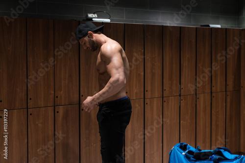 Poster Fit Man In Locker Room Opening Locker Door