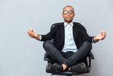 Fototapety Attractive young man in glasses meditating on office chair