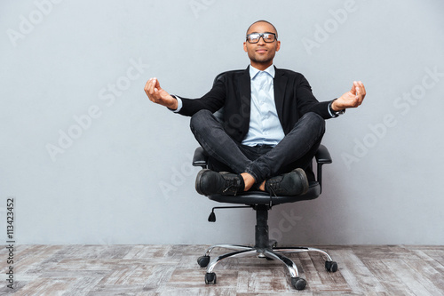 Leinwandbild Motiv Relaxed african young man sitting and meditating on office chair