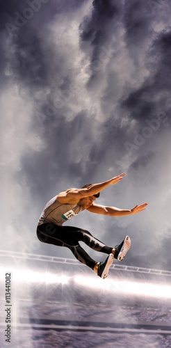 Portrait of sportsman jumping against a stadium