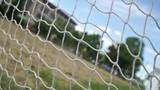 Beach football trough the goal net on cloudy sky background