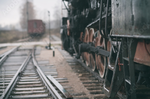 Plakát Vintage steam train and the track at the railway station on a cl