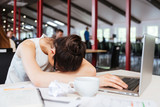 Exhausted fatigued young business woman sleeping on table at workplace