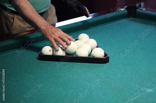 Staande foto Hands of man folding white billiard balls in triangle on green billiard table