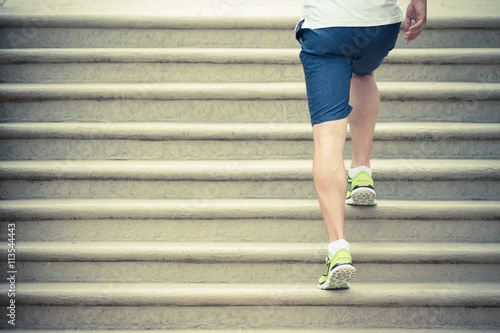 Close up of muscular male legs with sneakers running up the stairs. Sport, fitness, jogging, workout and healthy lifestyle concepts.