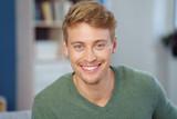 Fototapety lächelnder junger mann in seiner wohnung