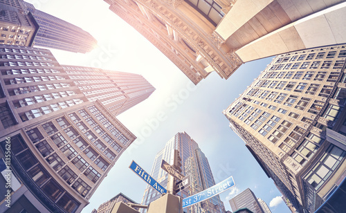 Vintage stylized fisheye lens photo of skyscrapers in Manhattan at sunset, New York City, USA.
