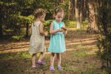 two little girls gather mushrooms