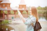 Back side of traveler girl searching right direction on map, orange sunset light, traveling along Europe