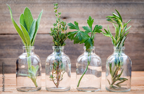 Bottle of essential oil with herbs rosemary, sage,parsley  and t