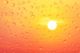 Raindrops on glass with colorful sunset and red sky background.