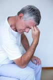 Upset senior man sitting on bed