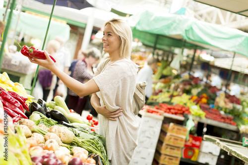 Keuken foto achterwand Boodschappen Young woman buying vegetables at the market