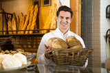 .Man selling fresh pastry and baguettes in local bakery