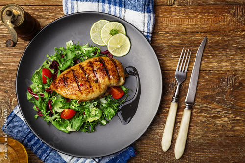 obraz PCV Grilled chicken breast with green salad on a black plate.
