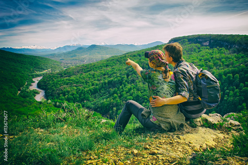 couple sits on the edge and looks to the mountains, girl points, the effect of the retro camera  © Den