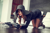 Sexy rich woman in hat and whip kneeling on floor