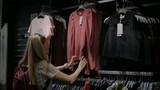 Woman Shopping for Clothing in low key light style