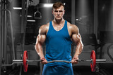 Muscular man working out in gym doing exercises with barbell at biceps, strong male