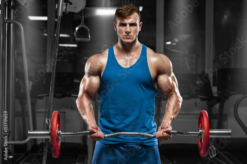 fototapeta na ścianę Muscular man working out in gym doing exercises with barbell at biceps, strong male