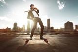 Geschäftsmann mit Smartphone auf Skateboard - 113708086