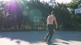 Young muscular man playing basketball in the park