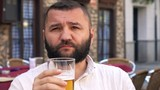 Young happy man drinking beer in cafe in the street in the city, 4K