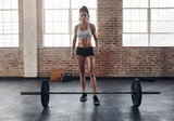 Fototapety Fit young woman standing at gym with barbells on floor