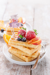 Homemade waffles with fruits, syrup and sugar on a white plate on a wooden background, closeup..