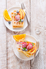Homemade waffles with fruits, syrup and sugar on a white plate on a wooden background, top view