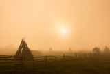 Pasture with haystacks in the foggy morning. - 113753284